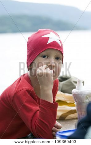 Portrait of fashionable teen boy in a red cap with white star.