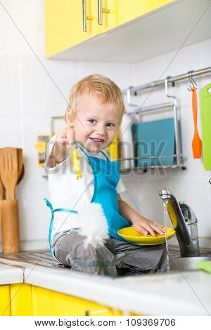 Happy toddler boy washing the dishes in the kitchen