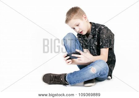 Teenager boy searching something on a smart phone isolated.