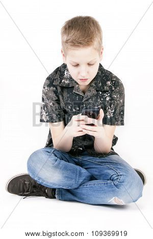 Teenager boy searching on a smart phone isolated.