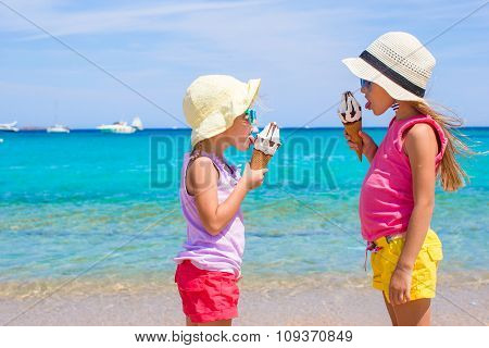Little adorable kids eating ice cream on tropical beach
