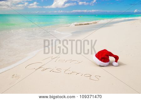 Santa Hat on sandy beach and Merry Christmas written in white sand