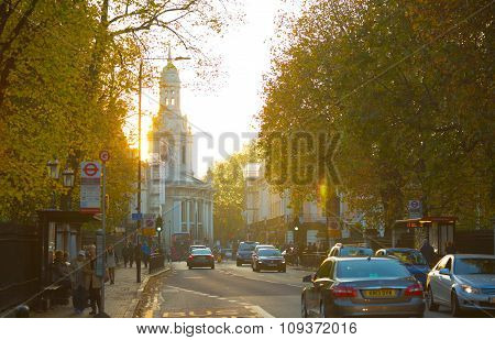 LONDON, UK - OCTOBER 31, 2015: Greenwich high street view at sunset with lots of cars and church on