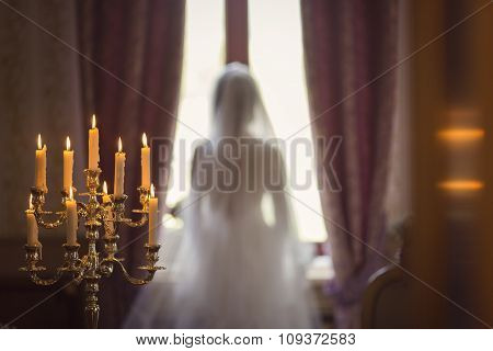 Portrait Of The Beautiful Bride Against A Window Indoors And Candles.