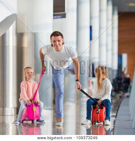 Adorable little girls with father in airport have fun waiting for boarding