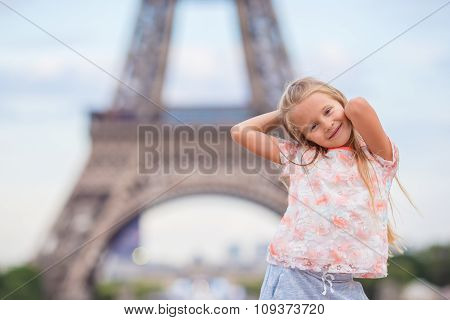 Adorable toddler girl in Paris background the Eiffel tower during summer vacation