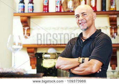 Portrait of sommelier or barman in front of bar background