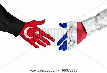 Turkey and France leaders shaking hands on a deal agreement