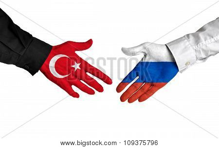 Turkey and Russia leaders shaking hands on a deal agreement