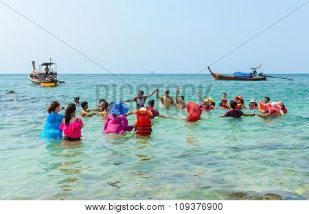 People Relaxing, Swimming, Having Fun On The Beach.