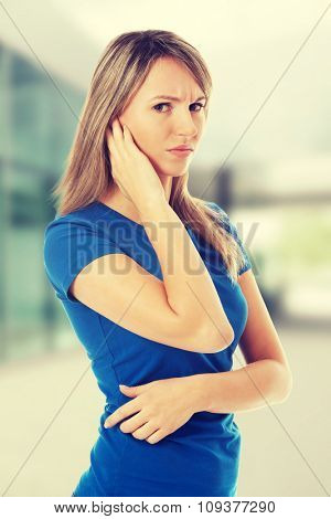 Young casual woman touching her ear