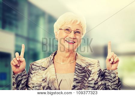 Old casual lady pointing up on copy space