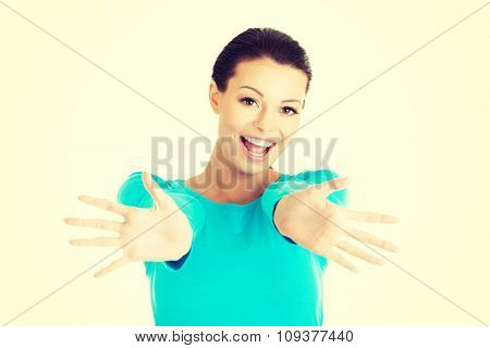 Portrait of a happy woman with open hands gesture.