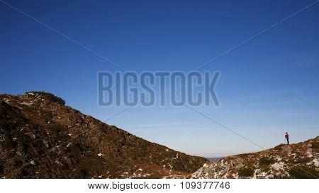 Silhouette Of Woman Running Along The Ridge.