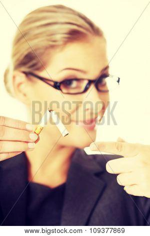 Woman breaking cigarette to stop smoking.