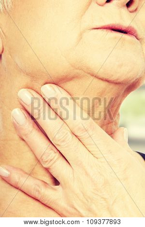 Close up on older woman's hand holding neck
