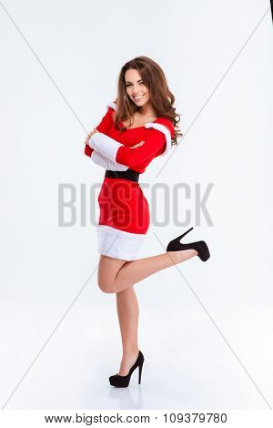 Full length portrait of a pretty smiling woman in santa claus cloth standing with arms folded isolated on a white background