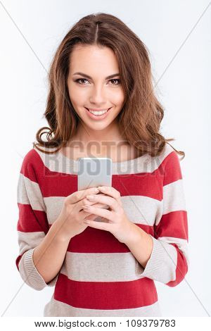 Portrait of a smiling woman using smartphone and looking at camera isolated on a white background