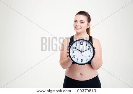 Portrait of a happy fat woman holding clock isolated on a white background