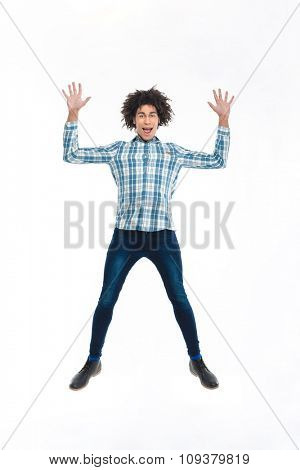 Full length portrait of a funny afro american man jumping isolated on a white background