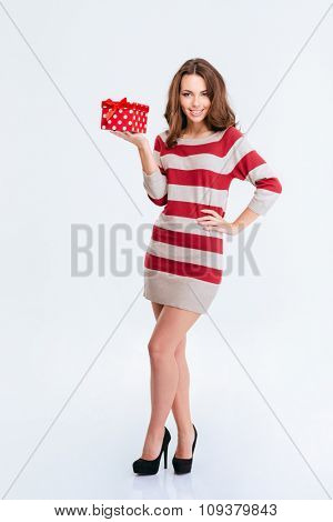 Full length portrait of a smiling woman in dress holding gift box isolated on a white background