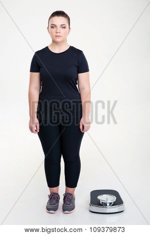 Full length portrait of a serious fat woman standing near weighing machine isolated on a white background