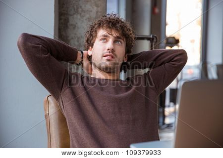 Pensive thoughtful dreaming curly attractive handsome man in brown sweetshirt holding hands behind head while sitting at his working place