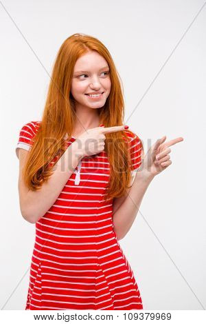 Cheerful beautiful happy young redhead woman in red striped dress pointing away while standing against white background
