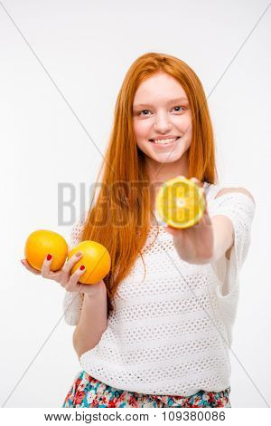 Portrait of pretty young woman holding juicy delicious orange
