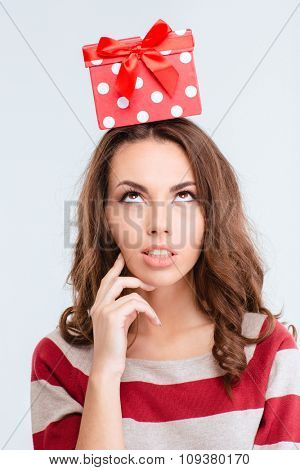 Portrait of a thoughtful woman looking up at gift box on head isolated on a white background