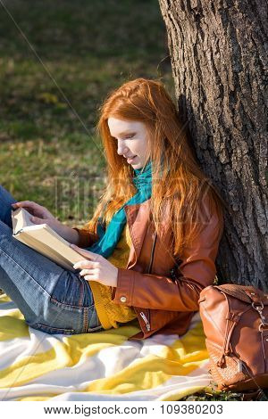 Concentrated smart girl with long red hair reading a book under the tree in park