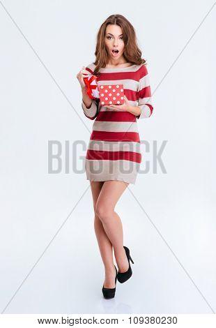 Full length portrait of amazed woman holding gift box isolated on a white background