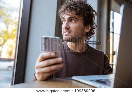 Thoughtful pensive handsome attractive young curly man in brown sweetshirt working with mobile phone and laptop