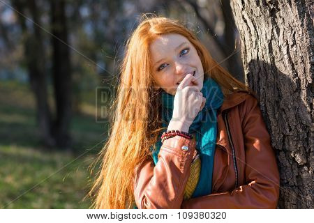 Pretty shy young redhead woman with long beautiful hair standing near the tree in park in autumn