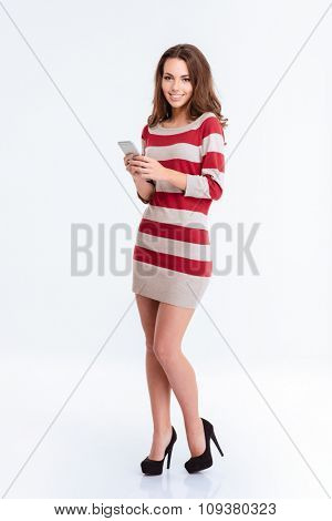 Full length portrait of a happy woman in dress using smartphone and looking at camera isolated on a white background
