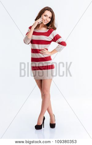 Full length portrait of a happy charming woman talking on the phone isolated on a white background