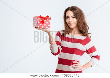 Portrait of a pretty smiling woman holding gift box isolated on a white background