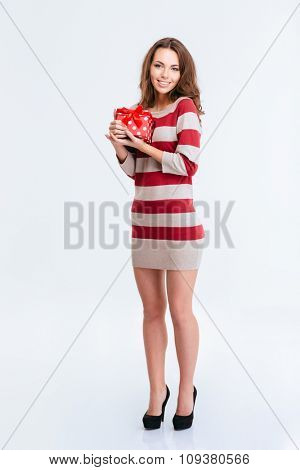 Full length portrait of a happy woman in dress holding gift box isolated on a white background