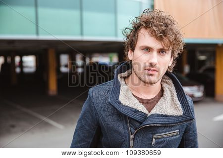Pensive handsome thoughtful attractive curly guy in black jacket staying on parking