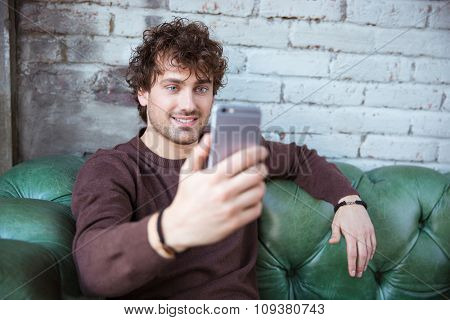 Curly handsome attractive smiling happy content guy in brown sweetshirt sitting on green leather couch and making selfie using mobile phone