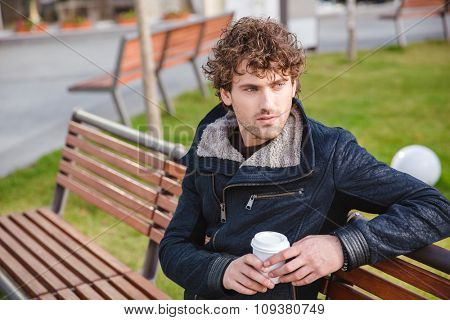 Handsome curly pensive young man in black jacket sitting on a wooden bench in the park and drinking coffee