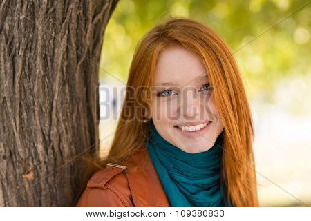 Closeup of young cheerful attractive woman standing near the tree in park
