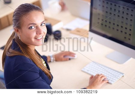 Young woman working in office, sitting at desk, using laptop