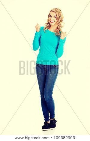 Full length woman making winner gesture.