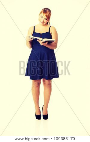Overweight woman in skirt reading a book