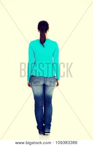 Full length woman standing back.