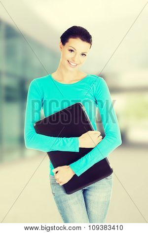 beautiful casual woman holding a laptop