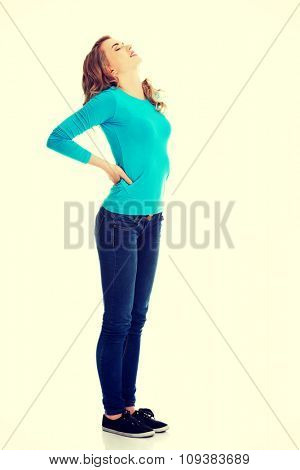 Full length woman with back pain.