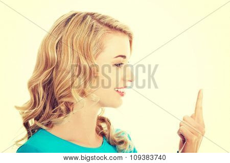 Side view of woman looking on her finger.