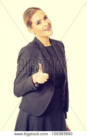 Young businesswoman gesturing thumbs up